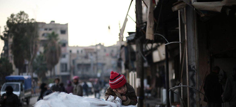 Una familia huye de un barrio azotado por la violencia en Ghouta, Siria, utilizando un carro para transportar sus pertenencias. Foto de archivo: UNICEF/Amer Al Shami