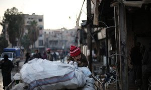 A family flees an active conflict neighbourhood in eastern Ghouta, Syria, using a cart to carry their belongings.