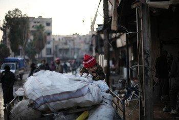 Una familia huye de un barrio azotado por la violencia en Guta, Siria, utilizando un carro para transportar sus pertenencias.