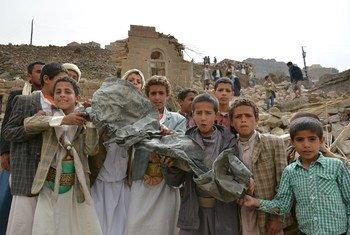 Des enfants montrent un morceau de métal tordu près de leurs maisons détruites par une attaque aérienne, dans le village d'Okash, près de Sana'a, au Yémen. Photo UNICEF/Mohammed Hamoud