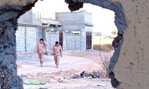 Deux soldats des forces opérant sous le gouvernement libyen basé à Tripoli marchant dans les rues désertes de Bin Jawad, près de l'important port pétrolier de Sidra.