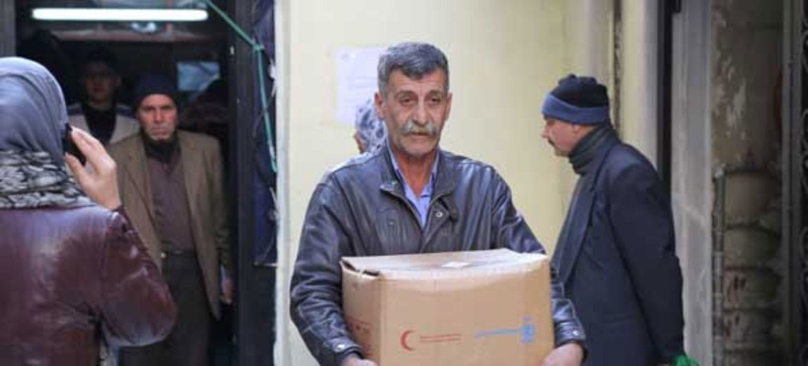 A Syrian man carries food provided by WFP.