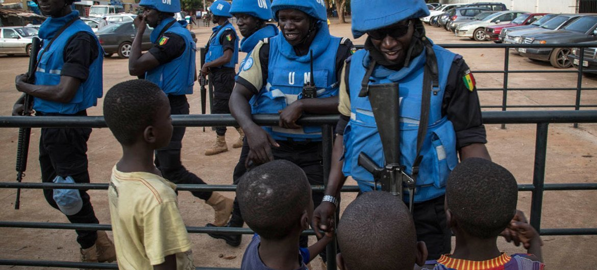 Peacekeepers with the United Nations Multidimensional Integrated Stabilization Mission in Mali (MINUSMA) are greeted by children.