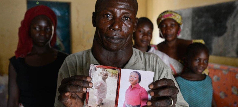 Un padre muestra las fotos de su hija mayor, de 18 años, y su hijo de 6 años, secuestrados por miembros de Boko Haram durante un ataque en su aldea en Yola, Nigeria. Foto: UNICEF/Sebastian Rich