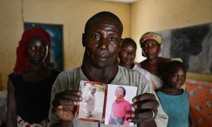 In the Gire 1 camp for internally displaced people, near Yola, Nigeria, a father holds photographs of his eldest daughter, 18, and his 6-year-old son, both of whom were kidnapped by members of Boko Haram during an attack on the family's village.
