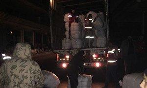 In Madaya, rural Damascus, Syrian Arab Red Crescent volunteers offload humanitarian emergency supplies.