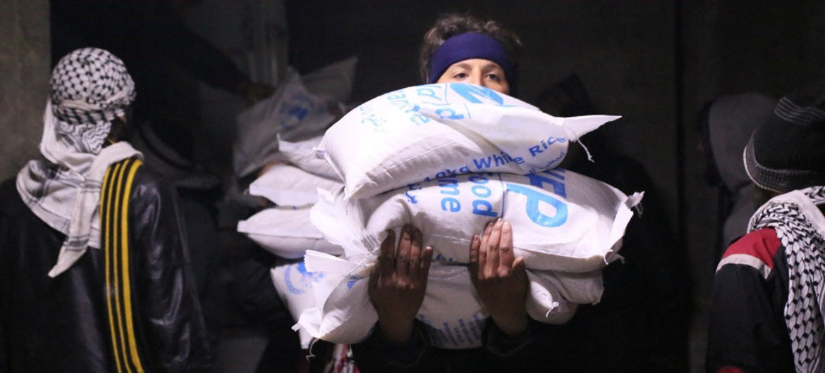 In Madaya, Syria, local community members help offload and distribute humanitarian aid supplies.