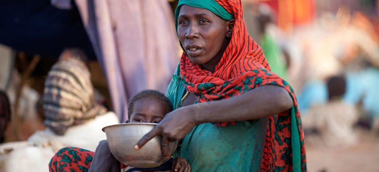 Une mère déplacée prépare de la nourriture pour son enfant près d'une base de la MINUAD à Um Baru, dans le Nord-Darfour. Photo : ONU/Hamid Abdulsalam