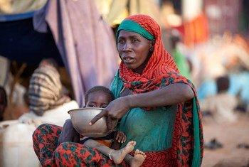Una madre desplazada alimenta a su hijo cerca de una base de UNAMID en Darfur del Norte. Foto de archivo: ONU/Hamid Abdulsalam