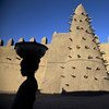 Residents of Timbuktu pass by Djingareyber Mosque, one of the historical architectural structures  along with Sankore Mosque, Sidi Yahia Mosque and sixteen mausoleums and holy public places  which together earned Timbuktu the designation of World Heritage Site by the UN Educational, Scientific and Cultural Organization (UNESCO).