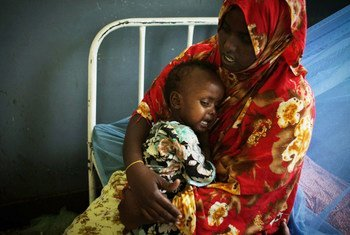 A mother cradles her malnourished and dehydrated baby at Banadir Hospital in the Somali capital Mogadishu 2011.