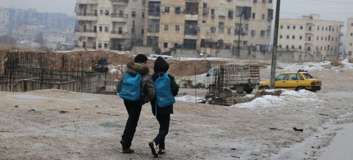 In Syria, two boys head home after school in East Aleppo in a snow day for the city.