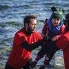 Voluntarios griegos ayudan a un niño pequeño a desembarcar al llegar a las costas de la isla griega de Lesbos, tras cruzar el mar Egeo desde Turquía. Foto: ACNUR/Achilleas Zavallis