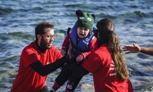 Greek volunteer life-guards help a young child out of a boat that reached the shores of Lesbos, having crossed the Aegean sea from Turkey.