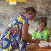 In Bangui on 14 February 2016, an electoral officer (right) assists a voter at a polling station for the Central African Republic's run-off presidential elections. A re-run of the 30 December 2015 legislative elections was also held.