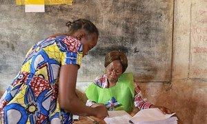 A Bangui le 14 février 2016, un agent électoral (à droite) aide une électrice dans un bureau de vote lors du second tour de l'élection présidentielle en République centrafricaine. Photo ONU/Nektarios Markogiannis