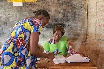 En Bangui, una asistente ayuda a una votante en una mesa electoral durante los comicios presidenciales en la República Centroafricana. Foto: ONU/Nektarios Markogiannis