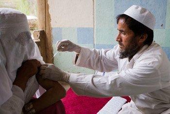 A doctor immunizes an Afghan woman against tetanus.