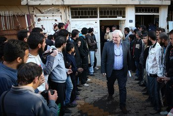 Le Secrétaire général adjoint aux affaires humanitaires, Stephen O'Brien (au centre) rendant visite à des habitants du quartier  d'Al Waer à Homs, en Syrie, in décelbre 2015. Photo OCHA/Bassam Diab