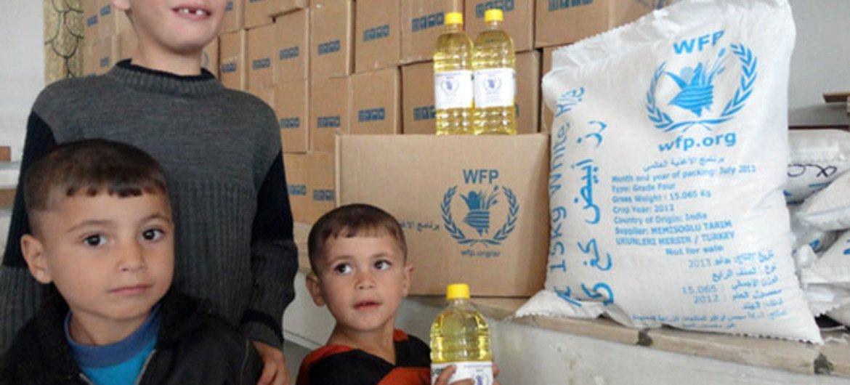 Una familia de Darayya, en Siria, recibe un paquete de alimentos del PMA. Foto: PMA/Hussam Alsaleh
