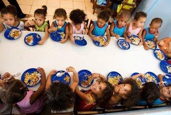 Niños comiendo en su colegio dentro de un programa escolar en América Latina.