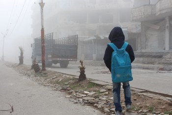 A child watches a truck carrying humanitarian aid for the besieged town of Moadamiyeh in February. In all, UNICEF delivered 16 truckloads of winter clothing and diapers.