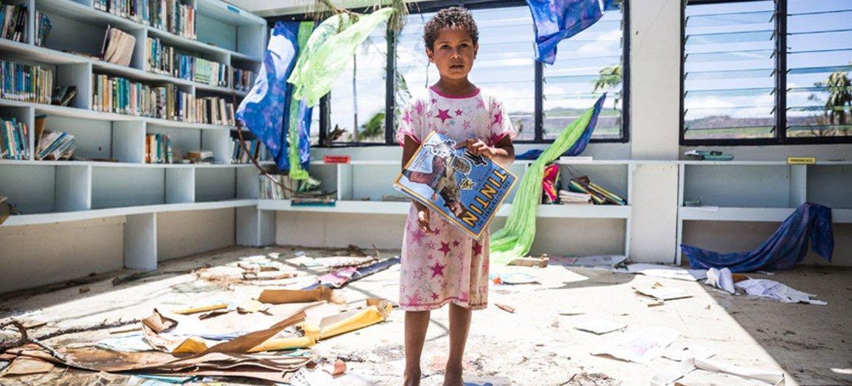 Una niña de siete años observa lo que ha quedado de la biblioteca del colegio de Nabau, en la provincia de Ra, Fiji. Foto: UNICEF/UN011701/Sokhin
