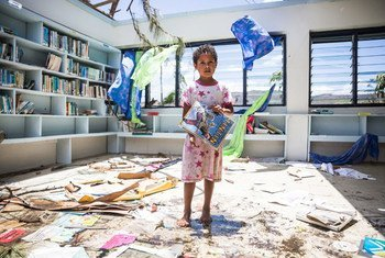 A seven-year old girl stands in the destroyed library of Nabau District School in Ra Province, Fiji.