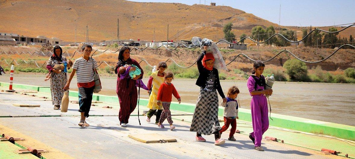 Des enfants et des femmes yézidis ayant fui la montagne de Sinjar reviennent en Iraq de Syrie via un poste frontière dans la ville de Peshkhabour, dans le gouvernorat de Dohuk.