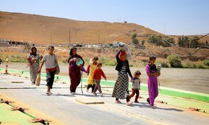 Yezidi children and women who fled Sinjar Mountain re-enter Iraq from Syria at a border crossing in the town of Peshkhabour in Dohuk Governorate.