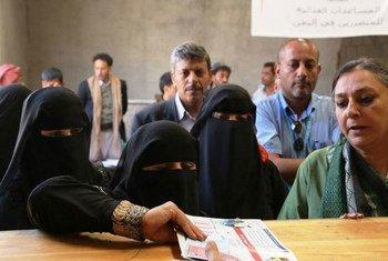 Des femmes yéménites reçoivent des bons alimentaires du Programme alimentaire mondial des Nations Unies (PAM) en présence du Représentant et Directeur pays du PAM au Yémen, Purnima Kashyap (à droite). Photo : PAM / Fares Khoailed