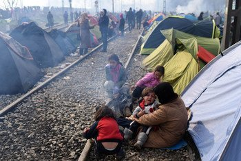 A mother holds her crying child, as her three other daughters sit by the fire outside their makeshift tent in Idomeni, Greece.