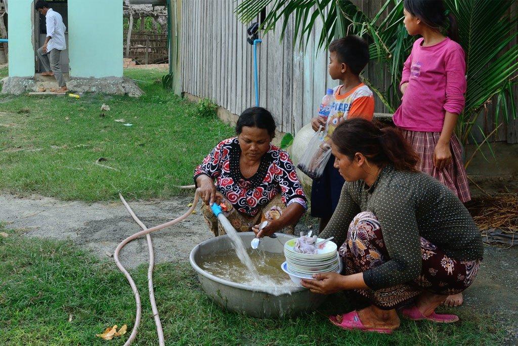 Women wash dishes in Kraing Serey village, Kampong Speu province, Cambodia.