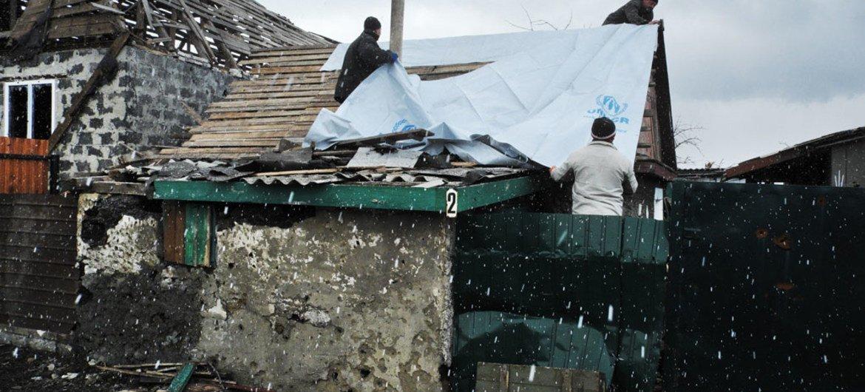 乌克兰东部顿涅茨克一个村庄的居民正在用联合国难民署提供的塑料布盖住在冲突中被损坏的房顶。图片来源:Iva Zimova