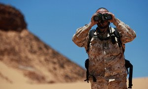 Un officer de liaison militaire de la Mission des Nations Unies pour l'organisation d'un référendum au Sahara occidental (MINURSO), observe au travers de ses jumelles lors d'une patrouille de surveillance du cessez-le-feu à Oum Dreyga, au Sahara occidental (juin 2010).  Photo ONU /Martine Perret