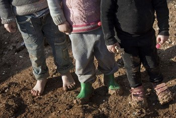 Syrian children, including one who is barefoot, stand atop the muddy ground in the Bab Al Salame camp for internally displaced persons, near the border with Turkey, in Aleppo Governorate.