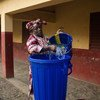 A teacher is preparing a bucket with water to use for hand washing. After being kept closed for three months due to the Ebola outbreak, schools across Guinea reopened on 19 January 2015.
