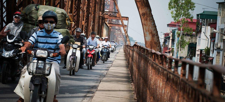 Une file de motos traverse le pont Long Bien sur la rivière Rouge à Hanoi, au Viet Nam. La moitié de la population mondiale vit en milieu urbain.