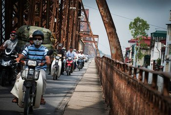 An array of motorbikes crossing Long Bien Bridge on the Red River in Hanoi, Viet Nam. Half of the world's population lives in urban environments.