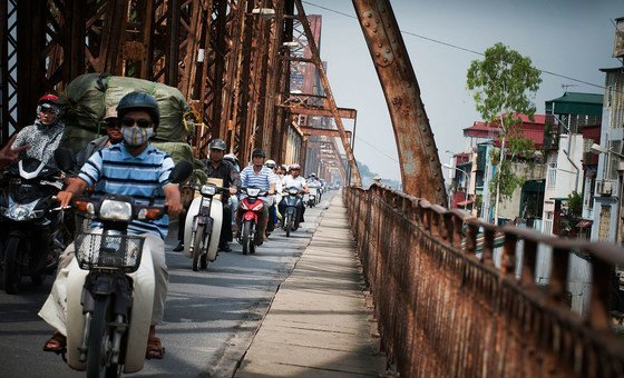 An array of motorbikes cross Long Bien Bridge on the Red River in Hanoi, Viet Nam.
