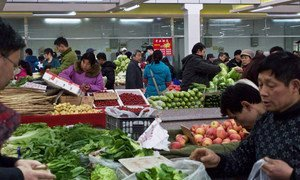 Shoppers in Beijing, China, buying fresh produce.