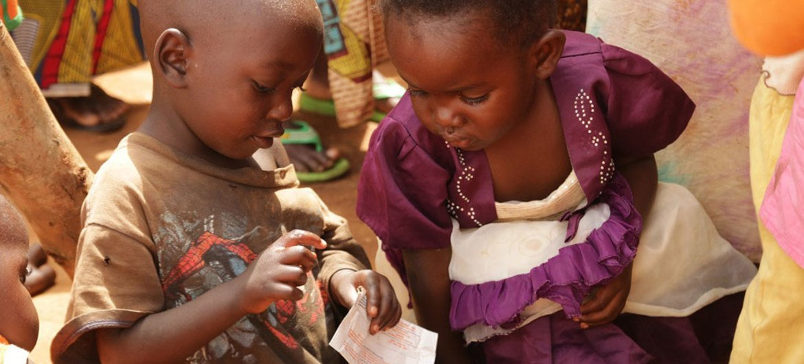 A young girl watches as a young boy eats from a sachet of ready-to-use therapeutic food (RUTF) in Mahama refugee camp, Eastern Province, Rwanda.