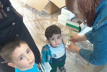 Сотрудники Агентства ООН оказывают помощь детям из семей палестинских беженцев в пригороде Дамаска, Сирия.