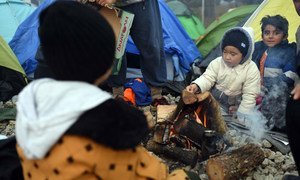 Two little boys warm up by a fire outside the camping tent that has been provided for them by humanitarian organisations in Idomeni, Greece.