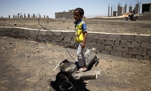 Boy playing on piece of exploded artillery shell which landed near his home, in the village of Al Mahjar, a suburb of Sana'a, Yemen.