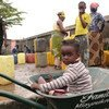 A child plays in a wheelbarrow while her family collects water into jerrycans in Brazzaville, the capital of the Republic of Congo.