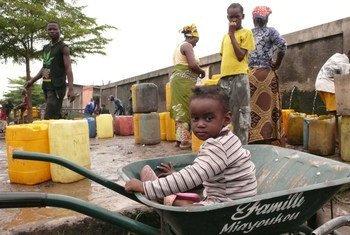 Un enfant joue dans une brouette pendant que sa famille recueille de l'eau dans des jerrycans à Brazzaville, la capitale de la République du Congo. Photo : UNICEF / Christine Nesbitt