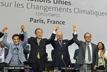 Secretary-General Ban Ki-moon (second left), UNFCCC's Christiana Figueres (left), French Foreign Minister Laurent Fabius and President of the UN Climate Change Conference in Paris (COP21), and President François Hollande of France (right), celebrate historic adoption of Paris Agreement.
