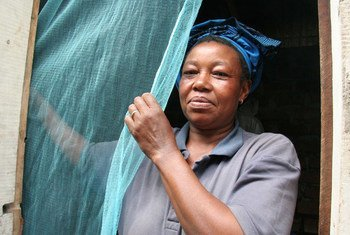 A woman putting up a mosquito bednet in Tanzania.