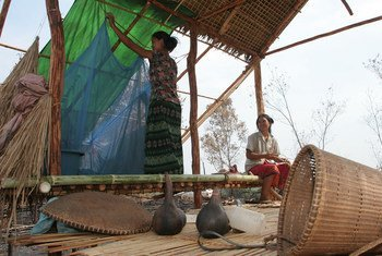 A woman hangs a mosquito net in the temporary dwelling in the fields (champka) that she and her husband are clearing to farm, Cambodia.